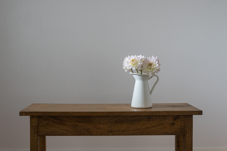 White dahlias in jug on wooden table against neutral wall background
