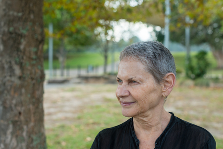 Portrait of beautiful older woman with short grey hair and black shirt in park (selective focus) Фото со стока