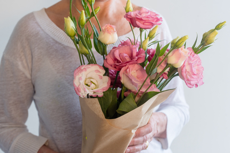 Close up of woman holding bouquet of pink lisianthus flowers wrapped in brown paper (selective focus)