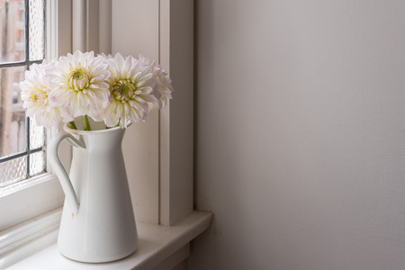 White dahlias in jug on window sill with moody light (selective focus)