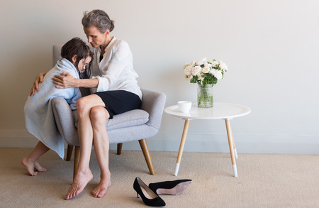 Middle aged mother in work clothes with shoes kicked off on floor cuddling daughter in blue bath towel
