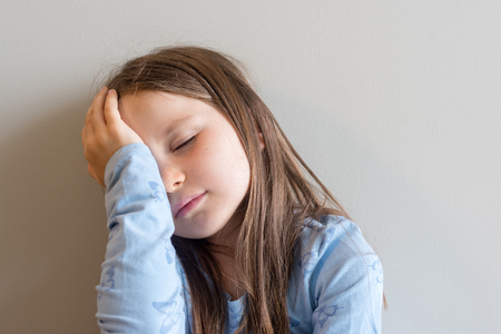 Close up of sad little girl in blue top with eyes closed and hand on head (selective focus)