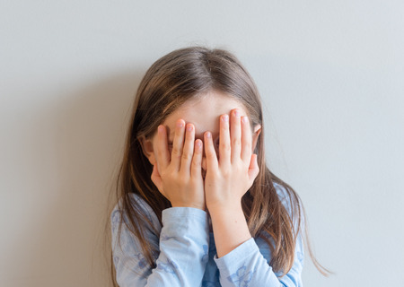 Head and shoulders view of little girl with hands covering face (selective focus)