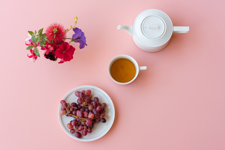 Directly above view of red grapes, white teacup and teapot, and colourful flowers on pink background (selective focus)