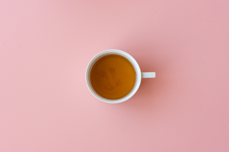 Directly above view of tea in cup on pink background Foto de archivo