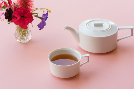 Tea and white teapot with colourful flowers on pink background