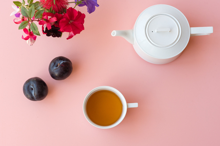 Directly above view of plums, white teacup and teapot and colourful flowers on pink background (selective focus)