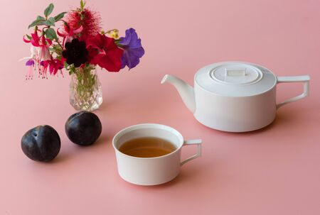 Plums, white teacup and teapot and colourful flowers on pink background (selective focus)