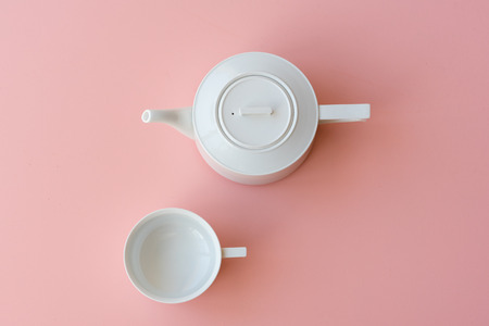 Directly above view of empty white tea cup and teapot on pink background
