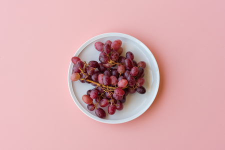 Directly above view of red grapes on pink background Foto de archivo