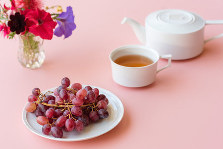 Red grapes, teacup, teapot and colourful flowers on pink background (selective focus)