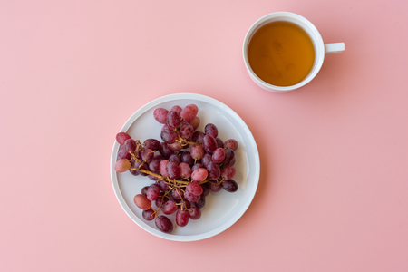 Directly above view of red grapes and white teacup on pink background