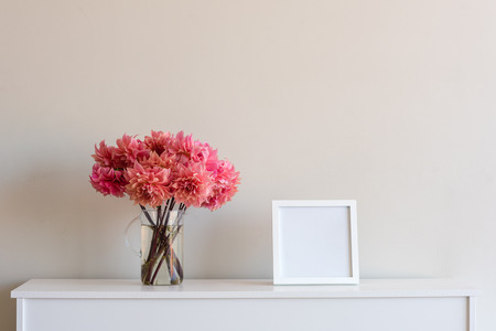 Bright coral pink dahlias in glass jug with blank square frame on white sideboard against neutral wall background