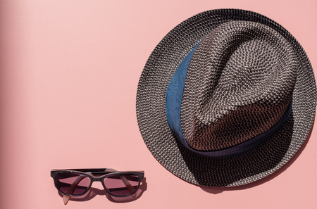 High angle view of tinted dark glasses and navy straw hat on pink background with shadows from bright sunlight (selective focus)