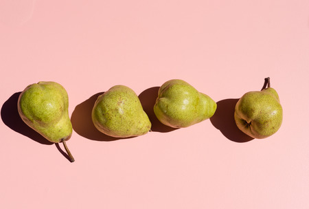 Directly above view of green pears on pink background with hard shadows from bright sunlight (selective focus)