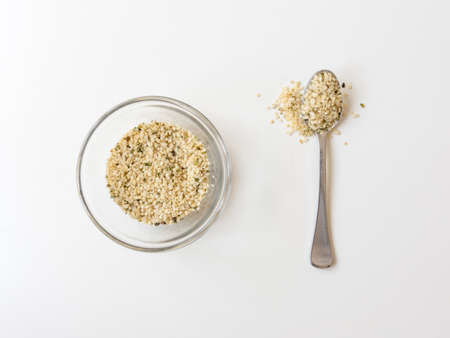 High angle close up view of hemp seeds in glass dish and heaped spoon on white background