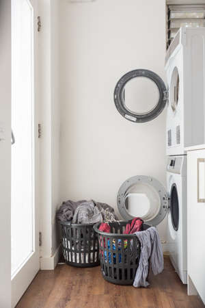 Overflowing washing baskets in galley laundry with washer and dryer (selective focus)
