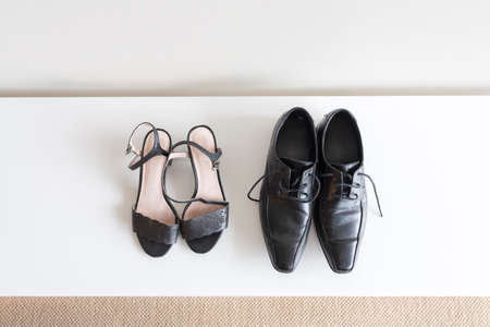 High angle view of women's and men's black shoes on white shoe rack - relationship concept
