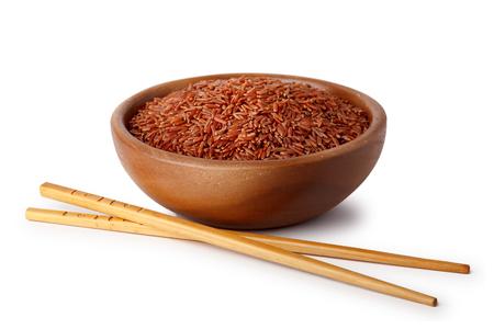 Un cuenco de madera con arroz rojo y palillos de comida. Productos naturales, comida sana.