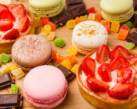 Background of sweets on a wooden board. Macaroons, cakes, chocolate, berries, candied fruits. Reklamní fotografie