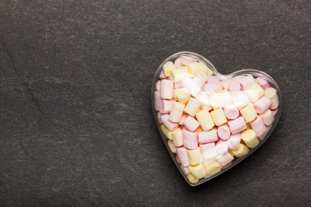 Marshmallow in a container in the form of a heart on a stone background. Sweets for Valentines Day. Reklamní fotografie