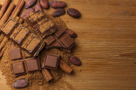 Cocoa beans, chocolate, cocoa powder and cinnamon on wooden background Reklamní fotografie