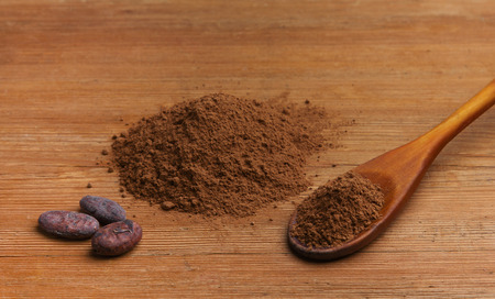 cocoa beans and cocoa powder on a wooden background