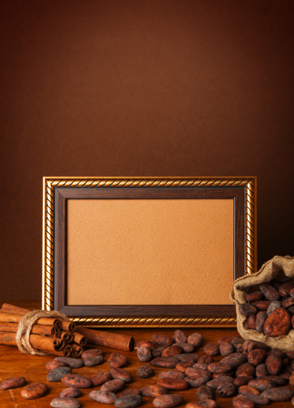 Cocoa beans, chocolate, cocoa powder, frame and cinnamon on wooden background Reklamní fotografie