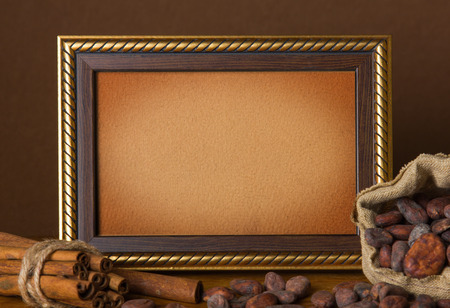 Cocoa beans, cinnamon and frame on wooden background