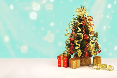 Decorated Christmas tree with gift boxes and snow lights bokeh, free copy space.