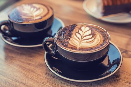 Two black cups of coffee with art on a table, blurred desert on the background