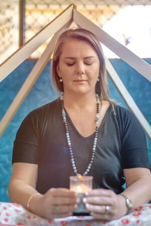Woman meditating with candle, sitting in a pyramid