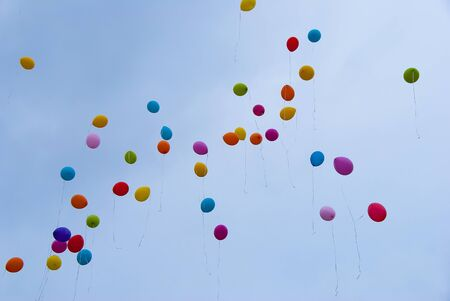 Many different color balloons flying in the sky