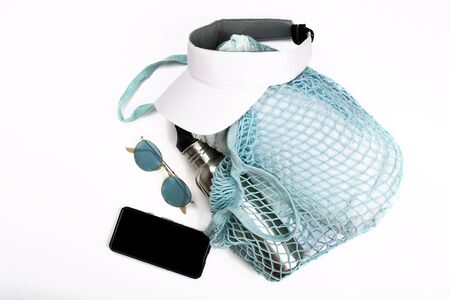 Bottle of water, mobile phone, sun glasses, beach towel and white visor in blue string mesh reusable bag on white background