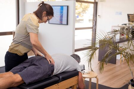 Man having chiropractic back adjustment. Physioterapy, osteopathy, alternative medicine pain relief rehabilitation Stok Fotoğraf