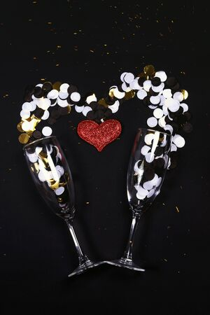 Champagne flutes with confetti and glitter heart on the black background, Valentines Day, love, New year