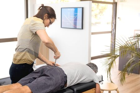 Man having chiropractic back adjustment. Physioterapy, osteopathy, alternative medicine pain relief rehabilitation Standard-Bild