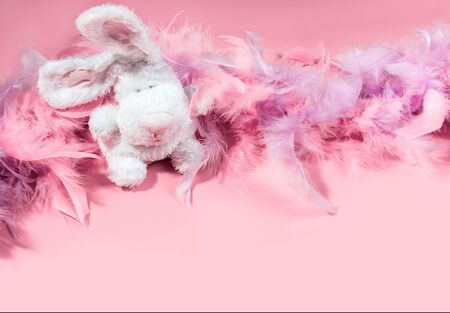 Toy Easter bunny rabbit with soft and gentle pink and violet feathers boa on pink background. Minimal Easter concept.