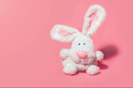 Adorable stuffed bunny on pink background with copy space. Minimal Easter concept.