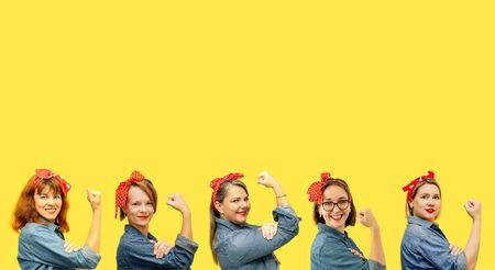 Women with a clenched fist rolling up their sleeves on yellow background, copy space, tribute to the icon Rosie Riveter. Girl power concept. Womens day.