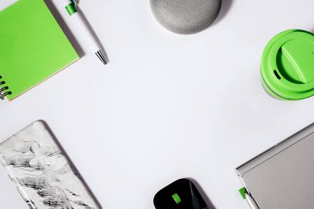 Digital Assistant concept. Flat lay of smart speaker with LED lights activated with cropped smartphone, green notepad, pen and reusable coffee cup.