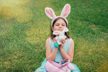 Cute little girl is wearing bunny ears on Easter day playing with colored eggs and bunny toy sitting on grass in garden.