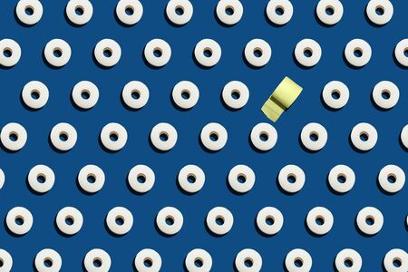 Pattern of rolls of many white toilet paper and one yellow on blue background. Nowel Corona virus infection background. Covid-19. Pandemic panic concept.