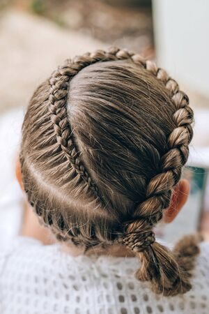 Back view of festive hairstyle from braid on a child girl with long hair.