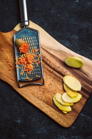 Ginger and turmeric roots with hand grater on wooden chopping board on black background.