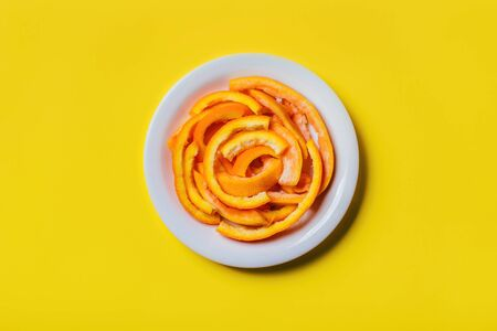 Citrus orange peels on a plate on yellow background. Imagens