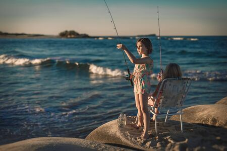 Two little girls are fishing in ocean surf at sunset. Summer leisure, hobby and fun for kids.