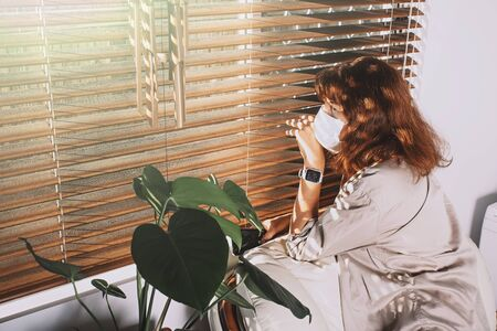 Middle-aged woman wearing a face mask and peeking out from blinds. Woman in quarantine looking through the window. Corona covid-19 virus protection. 版權商用圖片 - 150441929