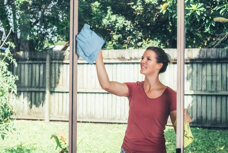 Young smiling woman is cleaning windows staying in the backyard, doing chores.