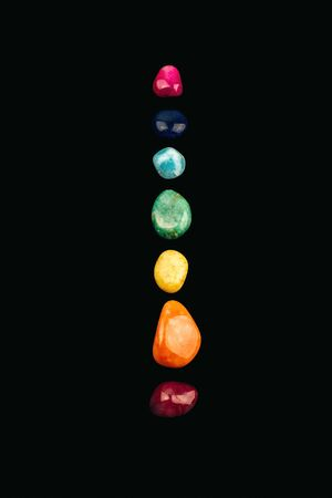 Chakra stones, crystals in a row on black background.